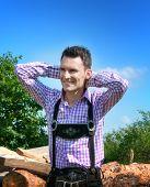 pic of lederhosen  - Young man wearing traditional Bavarian lederhosen posing in countryside - JPG