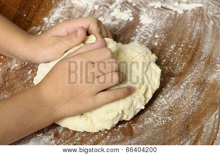 Child's Hands Kneading Bread Dough