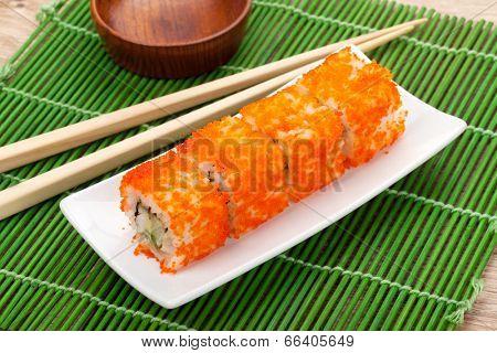 Sushi maki with tobiko on bamboo mat