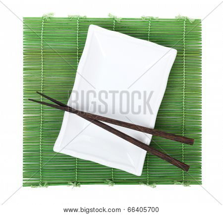 Chopsticks and plate over bamboo mat. Isolated on white background