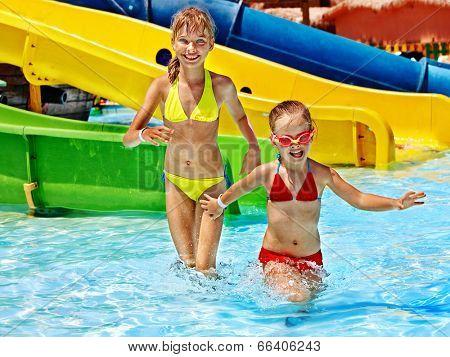 Children on water slide at aquapark. Summer holiday.