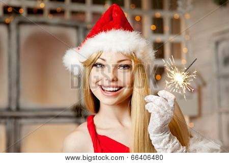 Young beauty smiling santa woman near the Christmas tree. Fashionable luxury girl celebrating New Year. Beautiful luxury trendy blonde.