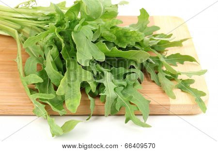 Fresh rucola salad or rocket lettuce leaves on wooden board isolated on white