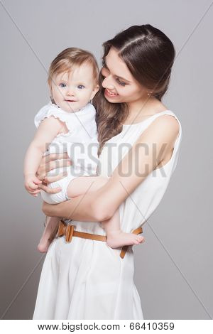 Young mother playing with little baby girl