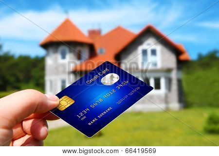 Hand Holding Credit Card With House As A Background