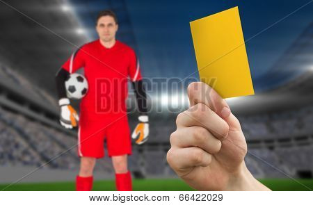 Hand holding up yellow card against football stadium with goalie
