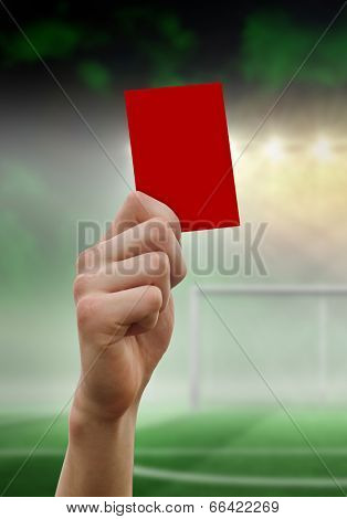Hand holding up red card against football pitch under spotlights