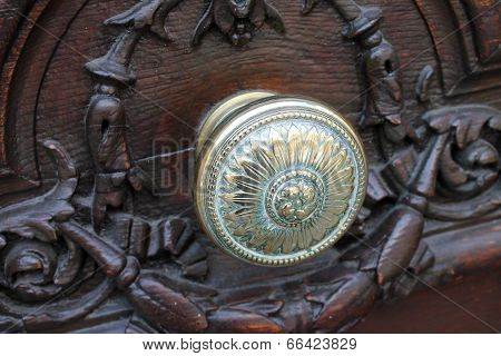 Ornate Brass Knob Set In A Massive Carved Wooden Door