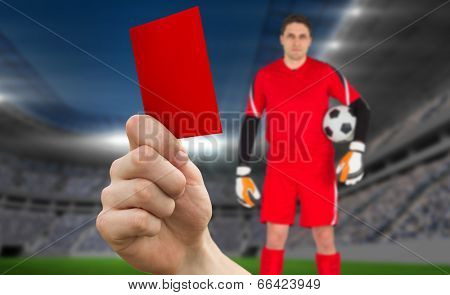 Composite image of hand holding up red card to goalie against football stadium