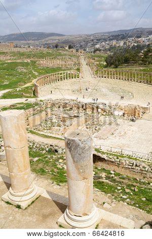 JERASH, JORDAN - MARCH 18, 2014: Tourists on the Oval Forum in the ancient city of Jerash. Since 2004, Jerash Archaeological City is included in UNESCO Tentative List