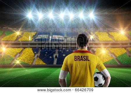 Brasil football player holding ball against stadium full of brasil football fans