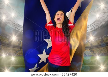 Cheering football fan in red holding bosnian flag against large football stadium with lights
