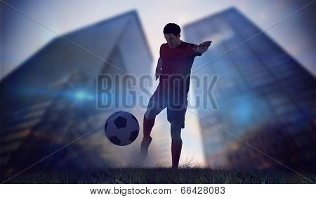 Football player in red kicking against low angle view of skyscrapers