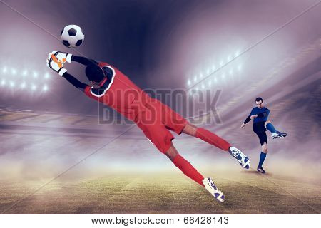 Goalkeeper in red making a save against football stadium