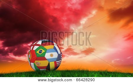 Football in multi national colours against green grass under red and purple sky