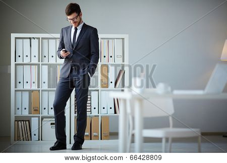 Handsome businessman in suit and eyeglasses writing sms in office