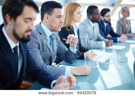 Pensive young businessman listening to explanations at seminar surrounded by other listeners