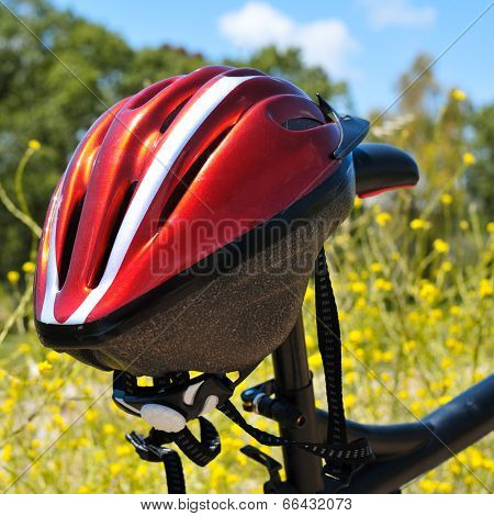 closeup of a red helmet hanging on a mountain bike in a spring landscape