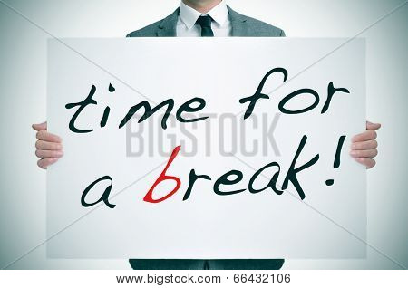 businessman holding a signboard with the text time for a break written in it