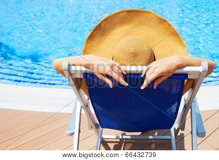 Young Woman Lying On Deckchair By Swimming Pool