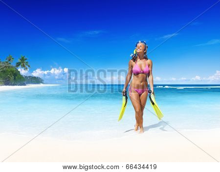 Smiling woman with scuba gear on a tropical beach.