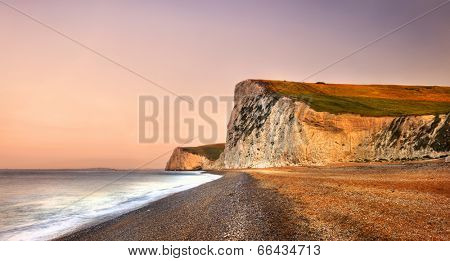 Durdle Door dramatic Jurrasic coastline at sunrise. Dorset, the UK.