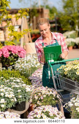 Garden center woman worker checking flowers writing inventory notes sunny