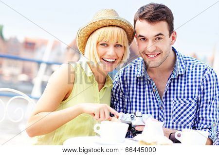 A picture of a young couple checking their camera in the cafe