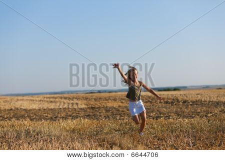 Girl running over a autumn field