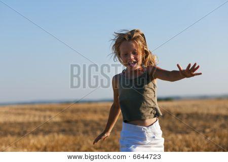 Girl running over a autumn field