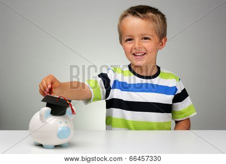 Young boy putting money into a piggy bank with a graduation mortar board cap concept for the cost of a college education