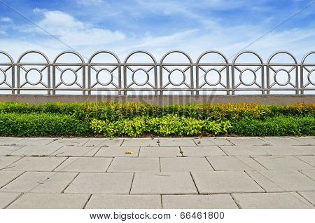 Shrubs And Stainless Steel Fence On Blue Sky Background