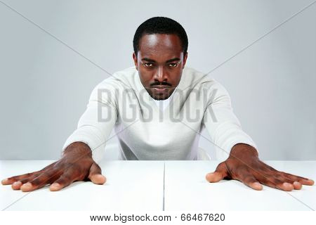 Serious african man sitting at the table on gray background