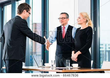 Business - young man in job interview for hiring, welcomes, Boss or Senior and his female Assistant in their office