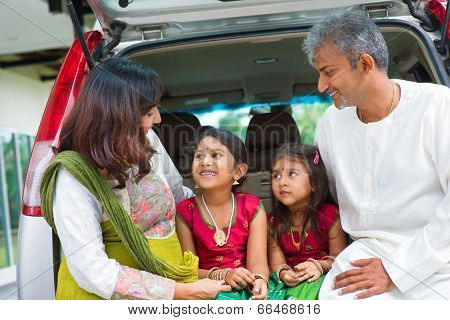 Happy Asian Indian family sitting in car talking and smiling happily, ready to summer vacation.
