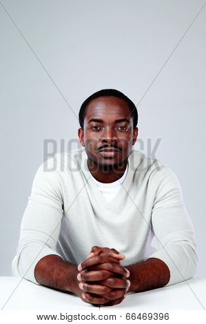 Pensive african man sitting at the table on gray background