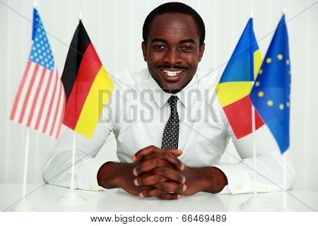 Happy businessman sitting at the table at his workplace
