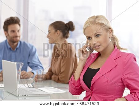Young businesswoman talking on mobilephone at businessmeeting.