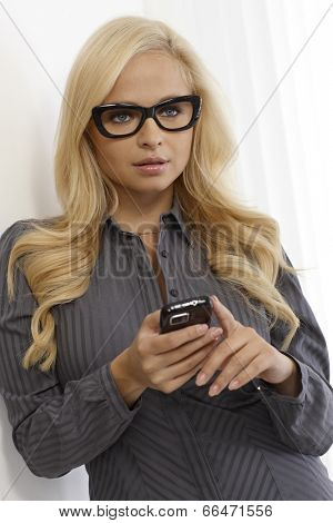 Beautiful blonde woman using mobilephone, wearing black framed glasses.