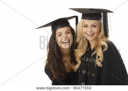 Happy female graduates hugging, wearing square academic cap, smiling.