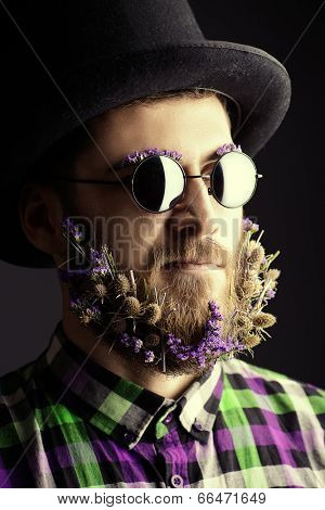 Strange young man with a beard of flowers wearing elegant bowler hat and glasses.