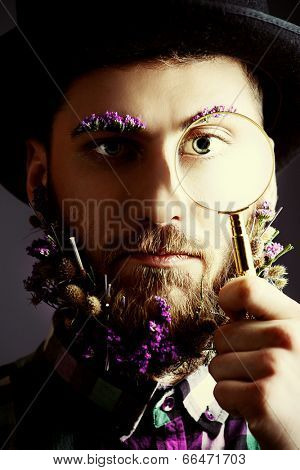 Strange young man with a beard of flowers wearing bowler hat and looking curiously through magnifier.