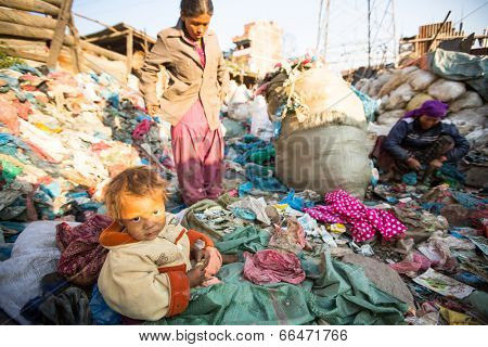 KATHMANDU, NEPAL - DEC 22, 2013: Unidentified child is sitting while her parents are working on dump. In Nepal annually die 50,000 children, in 60% of cases - malnutrition.