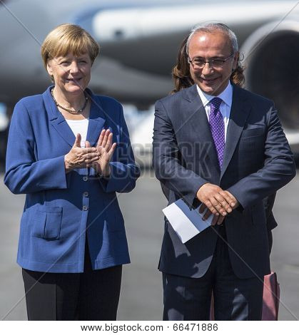 BERLIN, GERMANY - MAY 20, 2014: German Chancellor Angela Merkel (R) and Turkish Minister of transport Lutfi Elvan (R) open up the International aviation and space exhibition ILA.
