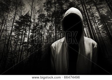 Portrait Of Dangerous Man Hiding Under The Hood In The Forest