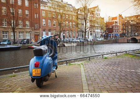 Amsterdam, Netherlands - March 19, 2014: Blue Vespa Scooter Stands Parked On The Canal Coast Embankm