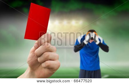 Hand holding up red card against football pitch under spotlights with goalie