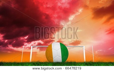 Football in ivory Coast colours against green grass under red and purple sky