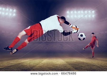 Fit goal keeper jumping up against large football stadium under blue sky