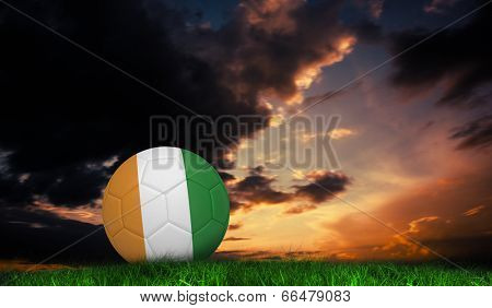 Football in ivory Coast colours against green grass under dark blue and orange sky